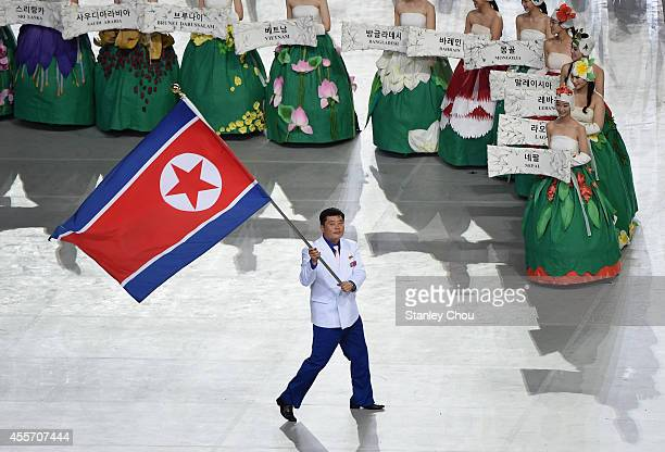 Sok Yongbom of North Korea carries the country's flag during the Opening Ceremony ahead of the 2014 Asian Games at Incheon Asiad Main Stadium on...