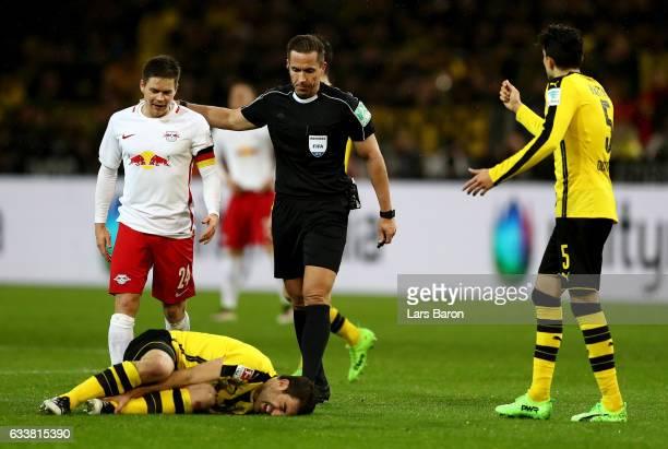 Sokratis of Dortmund lies injured on the pitch during the Bundesliga match between Borussia Dortmund and RB Leipzig at Signal Iduna Park on February...