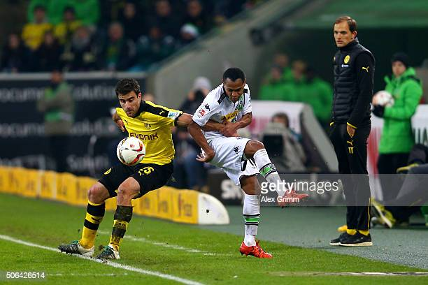 Sokratis Papastathopoulos of Borussia Dortmund and Raffael of Borussia Moenchengladbach tussle for the ball as Thomas Tuchel manager of Borussia...