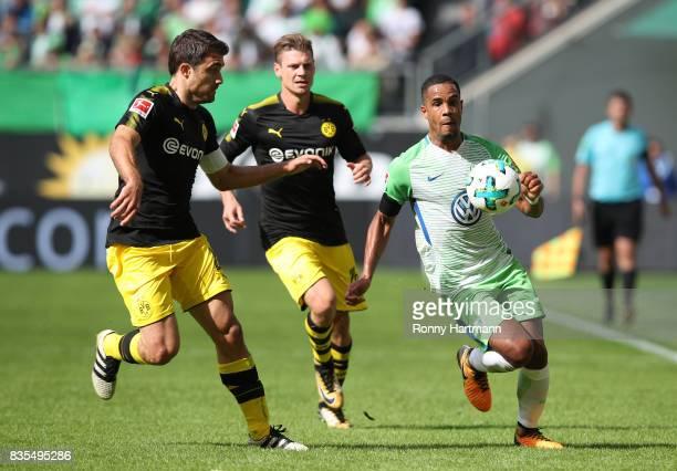 Sokratis Papastathopoulos of Borussia Dortmund Christian Pulisic of Borussia Dortmund and Daniel Didavi of VfL Wolfsburg during the Bundesliga match...