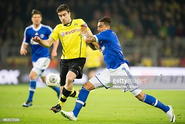 Sokratis Papastathopoulos of Borussia Dortmund in action against KevinPrince Boateng of Schalke 04 during the Bundesliga match between Borussia...
