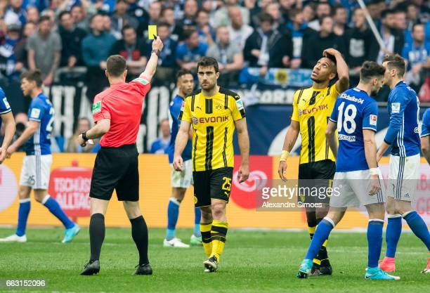 Sokratis Papastathopoulos of Borussia Dortmund receives the yellow card from referee Felix Zwayer during the to the Bundesliga match between FC...