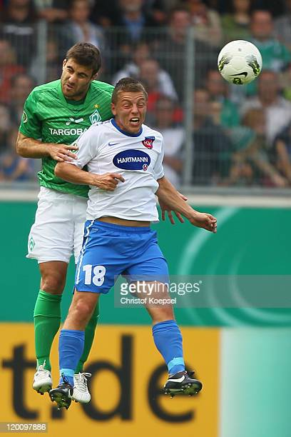 Sokratis Papastathopoulos of Bremen and Bastian Heidenfelder of Heidenheim go up for a headerduring the first round DFB Cup match between 1 FC...