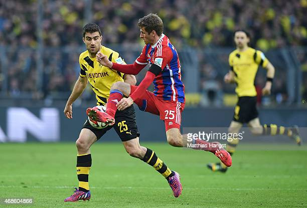 Sokratis Papastathopoulos of Dortmund and Thomas Mueller of Muenchen compete for the ball during the Bundesliga match between Borussia Dortmund and...