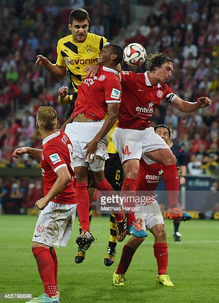 Sokratis Papastathopoulos of Dortmund jumps for a header with Junior Diaz of Mainz and Julian Baumgartlinger of Mainz during the Bundesliga match...