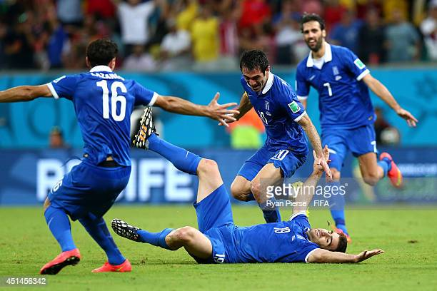 Sokratis Papastathopoulos of Greece celebrates scoring his team's first goal with his teammates Lazaros Christodoulopoulos Giorgos Karagounis and...