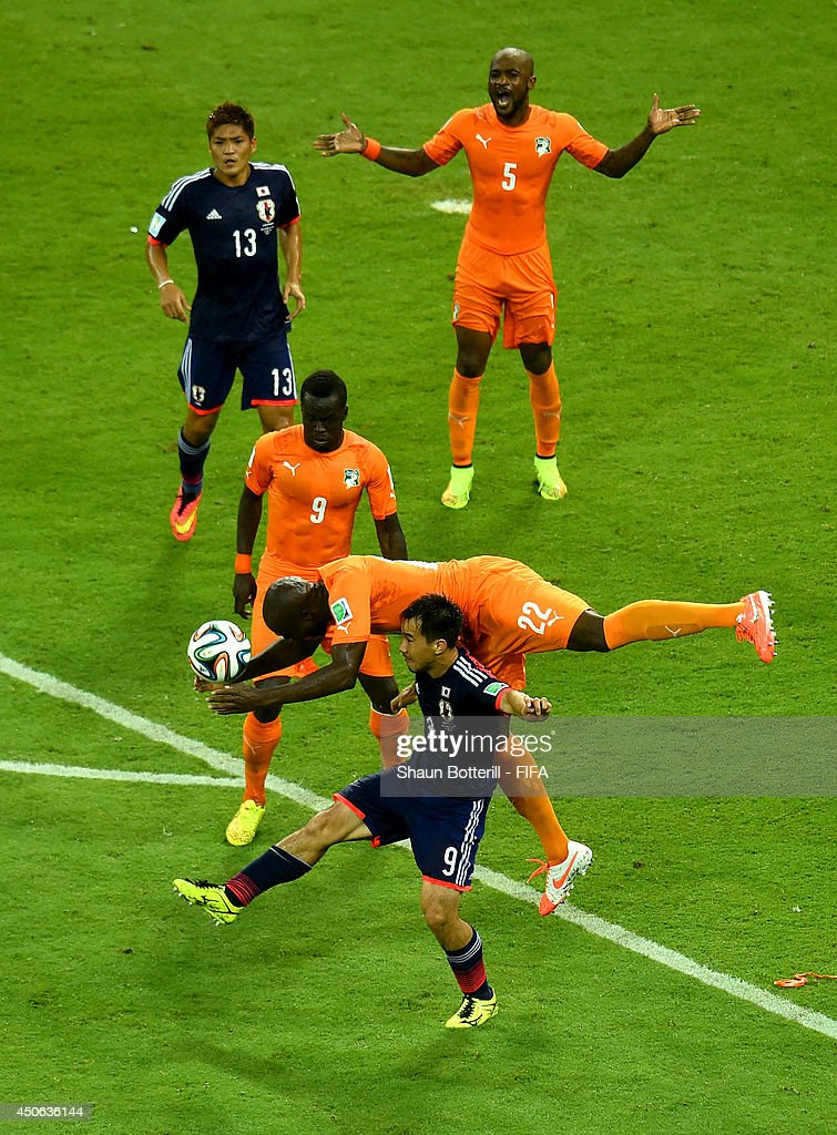 Sol Bamba of the Ivory Coast and Shinji Okazaki of Japan compete for the ball during the 2014 FIFA World Cup Brazil Group C match between Cote...