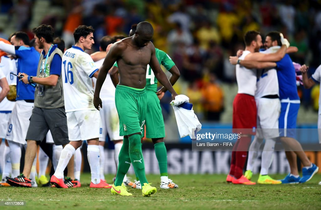 Sol Bamba of the Ivory Coast walks off the pitch while Greece players celebrate after the 2014 FIFA World Cup Brazil Group C match between Greece and...