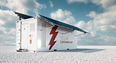 Solar container unit. 3d rendering concept of a white industrial battery energy storage container with mounted black solar panels situated on white gravel in empty landscape in sunny weather.