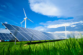 Solar energy panels and windmills against blue sky on summer day, background