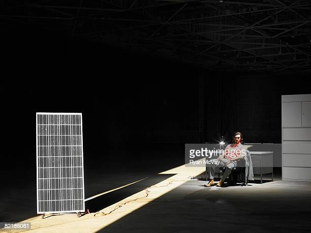 solar panel and man sitting at desk