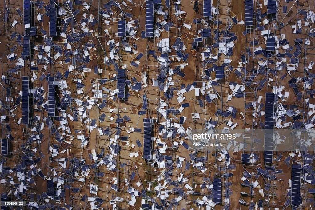 TOPSHOT - Solar panel debris is seen scattered in a solar panel field in the aftermath of Hurricane Maria in Humacao, Puerto Rico on October 2, 2017. President Donald Trump strenuously defended US efforts to bring relief to storm-battered Puerto Rico, even as one island official said Trump was trying to gloss over 'things that are not going well,' two weeks after devastating Hurricane Maria left much of the island without electricity, fresh water or sufficient food. / AFP PHOTO / Ricardo ARDUENGO