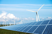 solar panel in green lawn with wind power station in blue sky