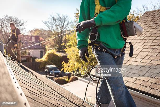 Solar panel installation crew on roof of house