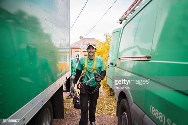 Solar panel installation worker walking in between truck and van