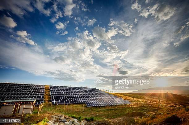 Panneaux solaires et champ vert sous le spectaculaire ciel au coucher du soleil