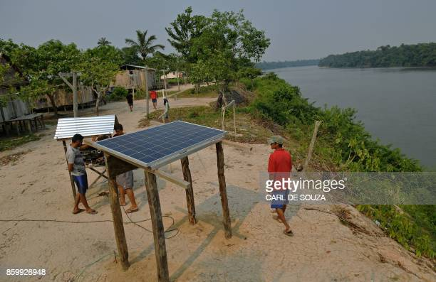 Solar panels donated by the World Wildlife Fund and Brazilian government are installed in the village of Volta do Bucho in the Western Amazon region...