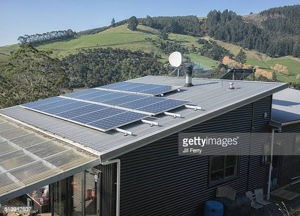 Solar panels for electricity and a solar hot water panel on the roof of a self sufficient house Water is also heated by a wood burner