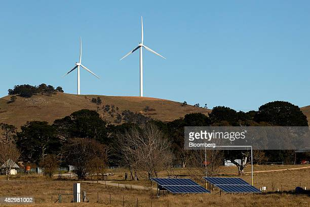 Solar panels stand in a field in front of wind turbines at the Woodlawn Wind Farm operated by Infigen Energy in Bungendore New South Wales Australia...