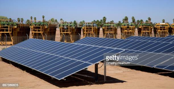 Solar panels with cotton balers in the background