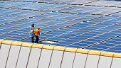 A Technician installing a solar panels on the factory roof.