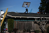 SolarCraft worker Craig Powell carries a solar panel on the roof of a home on February 26 2015 in San Rafael California According to a survey report...
