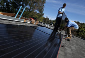 SolarCraft workers Craig Powell and Edwin Neal install solar panels on the roof of a home on February 26 2015 in San Rafael California According to a...