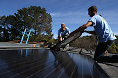 SolarCraft workers Joel Overly and Craig Powell install a solar panel on the roof of a home on February 26 2015 in San Rafael California According to...