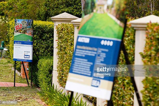 A 'Sold' Harcourts International Ltd auction sign left stands on display outside a house in the suburb of Beacon Hill in Sydney Australia on Saturday...