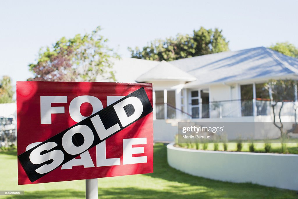Sold sign in front yard of house : Stock Photo
