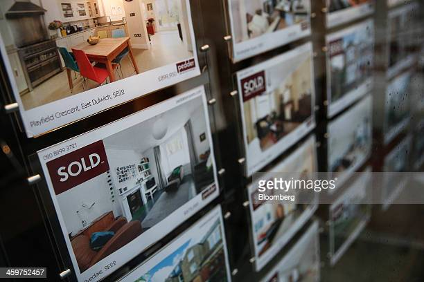 'Sold' signs sits on photographs of a residential properties in an estate agent's window display in London UK on Monday Dec 30 2013 UK house prices...