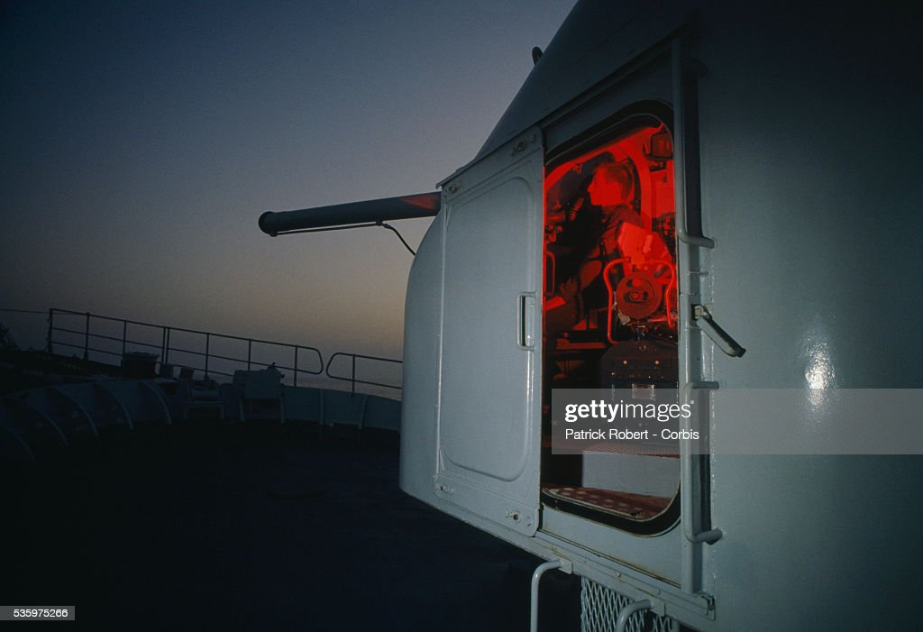 A soldier aboard the French gunboat Doudart de Lagree patrols the Persian Gulf during the Iran-Iraq War. French naval ships were used during the war to protect Kuwaiti oil tankers, which became targets as fighting escalated between Iraq and Iran.