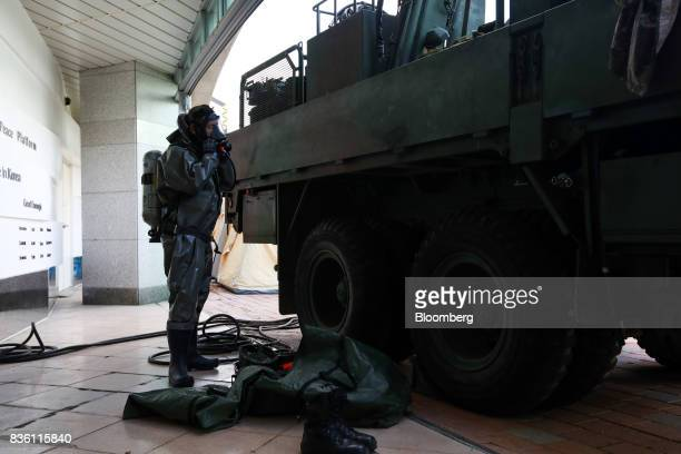 A soldier adjusts his gas mask while standing next to a military vehicle during a simulated chemical terrorism crisis as part of an antiterror drill...