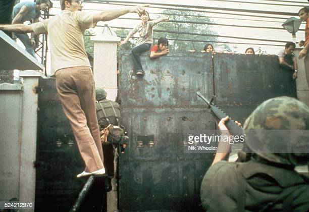 A soldier aiming his gun at South Vietnamese people climbing the gates of the United States Embassy in Saigon South Vietnam
