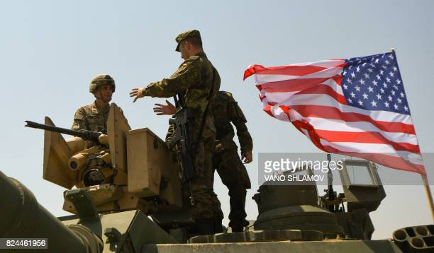 A US soldier and a German soldier talk while standing on an Abrams Battle Tank bearing the US flag prior to the opening ceremony of the joint...