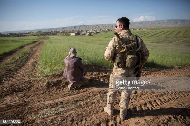 A soldier and a scout secure an area near Mosul on April 20 2017 in Mosul Iraq