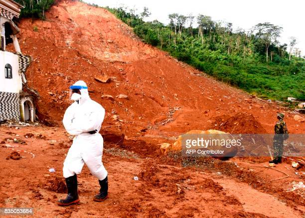 A soldier and disaster relief volunteer walk along a partiallycollapsed hillside on August 18 2017 in Freetown following heavy rains which resulted...