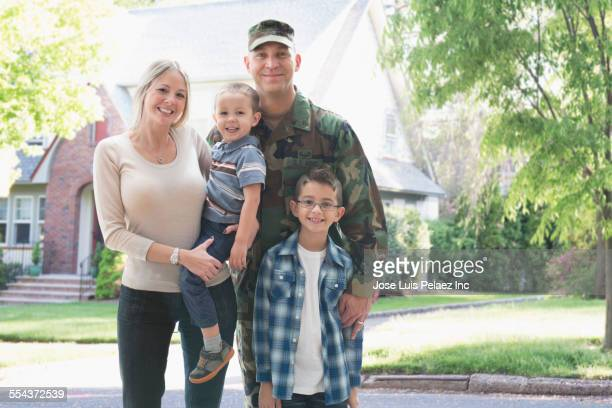 Soldier and family smiling outside suburban house