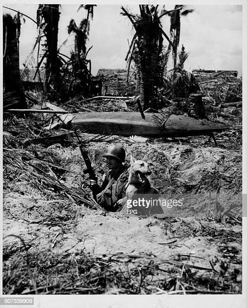 A US soldier and his dog pinned down in a shallow foxhole by enemy fire during World War Two Leyte Island Philippines circa 1943
