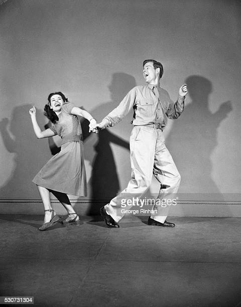 A soldier and his girl are shown jitterbugging in the 1940s They are facing away from each other as they hold each other's hand and have gleeful...
