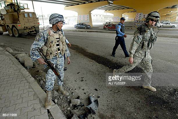 A US soldier and Iraqi police commandos inspect the site where a roadside bomb targeted an Iraqi police patrol in Baghdad on March 13 2009 Four Iraqi...