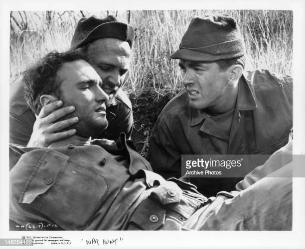 Soldier and Tom Skerritt give support to another wounded soldier in a scene from the film 'War Hunt' 1962