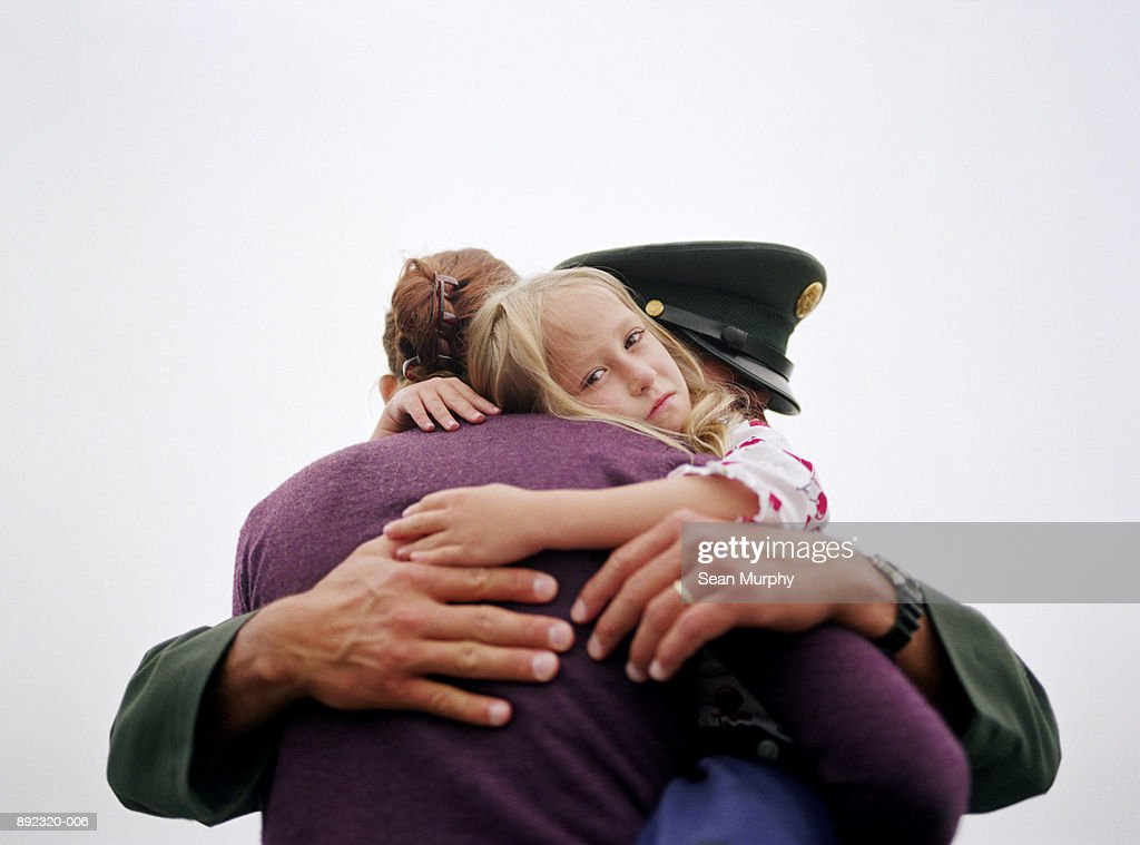 Soldier and wife embracing, daughter (5-7) in between : Stock Photo