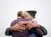 Soldier and wife embracing, daughter (5-7) in between
