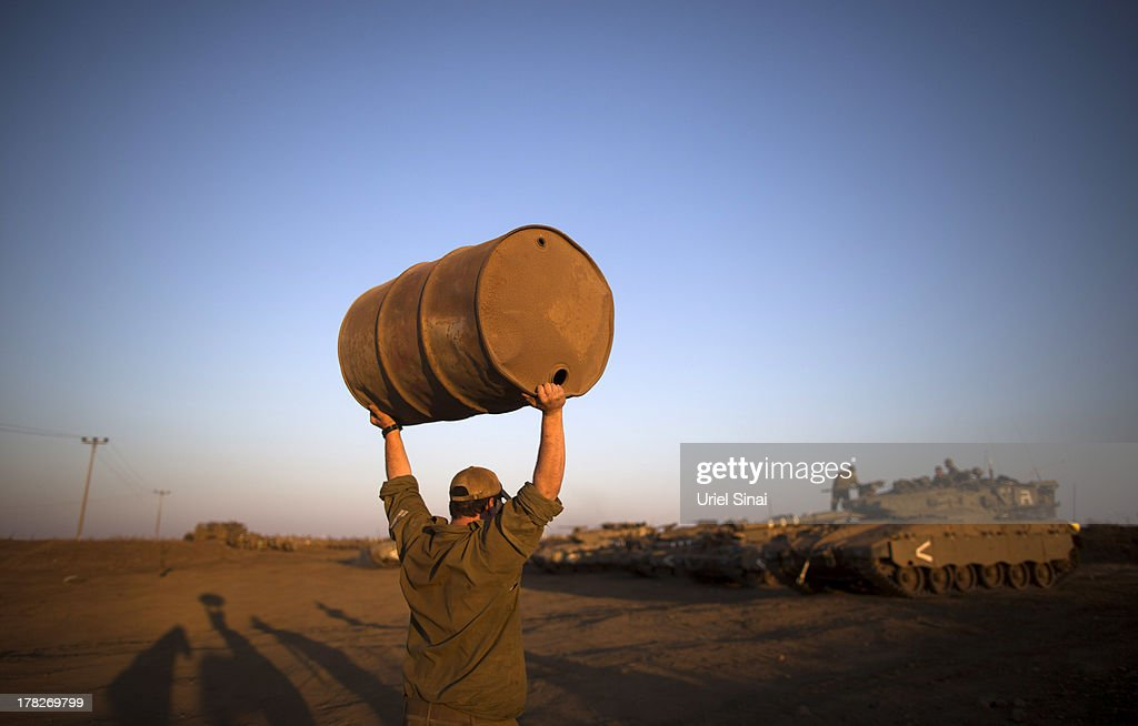 A soldier carries a barrels as Israeli troops start preparations at a deployment area during a military exercise on August 28, 2013 near the border with Syria, in the Israeli-annexed Golan Heights. Tension is rising in Israel amid talks of an international military intervention In Syria following reported chemical weapons attacks.