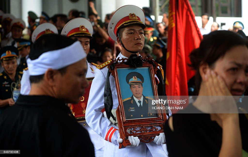 A soldier carries a portrait before the coffin (not pictured) of one of the victims of a rescue aircraft that crashed on June 16, 2016 over the South China Sea during a search mission for a Vietnamese Airforce Sukhoi SU-30MK2 that went missing two days earlier, during an official funeral ceremony in Hanoi on June 30, 2016. / AFP / HOANG