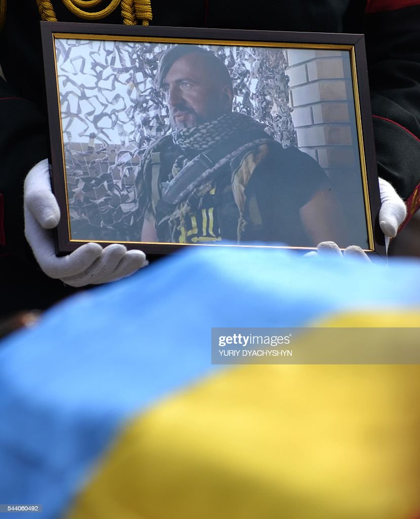 A soldier carries a portrait of Wassyl Slipak as people take part in his funeral ceremony in the western Ukrainian city of Lviv on July 1, 2016. A Ukrainian opera singer who performed for two decades in France before joining Kiev's volunteer forces fighting pro-Russian insurgents has been killed in the separatist east, officials said on June 29. Wassyl Slipak, a baritone who was born in 1974, left France and joined the armed wing of Ukraine's ultranationalist Pravy Sektor (Right Sector) party shortly after a war that has claimed more than 9,440 lives broke out in April 2014, according to his website. Slipak originally performed at the Lviv Conservatory in western Ukraine before passing an entrance exam at the prestigious Paris Opera and launching his career in France. / AFP / Yuriy Dyachyshyn
