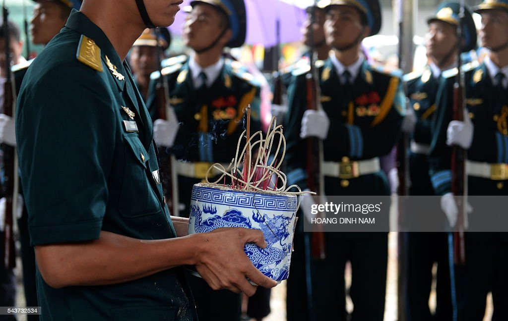 A soldier carries a pot with burning incense sticks before the coffin (not pictured) of one of the victims of a rescue aircraft that crashed on June 16, 2016 over the South China Sea during a search mission for a Vietnamese Airforce Sukhoi SU-30MK2 that went missing two days earlier, during an official funeral ceremony in Hanoi on June 30, 2016. / AFP / HOANG