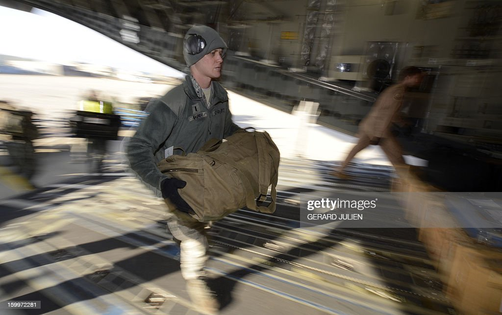 A US soldier carries French equipment on board a C17 aircraft of the US Airforce carriying French armoured vehicles at the Istres military airport (BA 125) on January 24, 2012 in Istres, southern France, prior to take off and heading toward Mali as part of the 'Serval' operation.