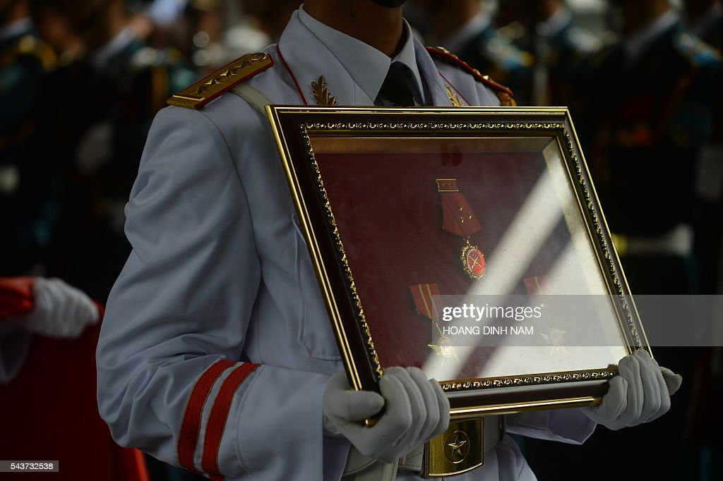 A soldier carries military decorations before the coffin (not pictured) of one of the victims of a rescue aircraft that crashed on June 16, 2016 over the South China Sea during a search mission for a Vietnamese Airforce Sukhoi SU-30MK2 that went missing two days earlier, during an official funeral ceremony in Hanoi on June 30, 2016. / AFP / HOANG